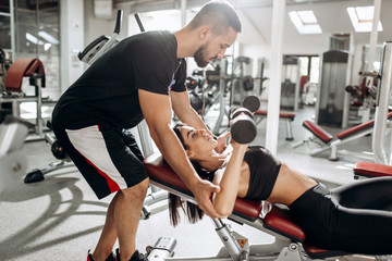 Beautiful athletic girl dressed in black sports top and tights builds up muscles with dumbbells under the supervision of a coach in the gym