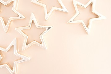 Christmas composition. Xmas gold stars on pastel beige background. Flat lay, top view, copy space