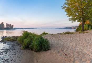 Section of plain river with sandy bank autumn at sunrise