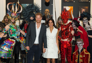 Britain's Prince Harry and Meghan, the Duke and Duchess of Sussex, pose for a photo with actors in costume during a visit to Courtenay Creative, in Wellington