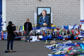 A man poses for a photo next to flowers outside Leicester City's King Power stadium, after the club's owner Thai businessman Vichai Srivaddhanaprabha and four other people died when the helicopter they were travelling in crashed in Leicester
