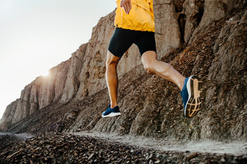 man athlete running on mountain trail in sunlight
