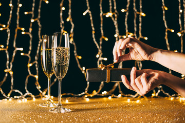 cropped image of woman opening christmas present near champagne in glasses on garland light background