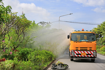 Truck watering a tree by spray water in the park at the morning.