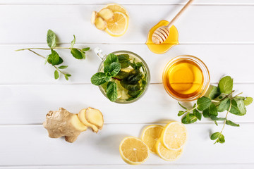 Ginger green tea in a glass for flu cold winter days. Side view on white wooden background decorated with mint, lemon and honey