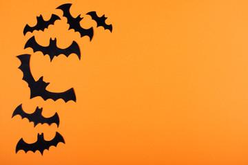 Flock of paper bats on orange wall.