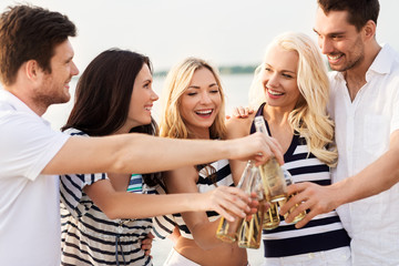 friendship, summer holidays and people concept - group of happy friends in striped clothes drinking non alcoholic beer on beach