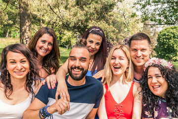 group photo of friends taken with a mobile selfie stick. seven people take self portrait outdoor