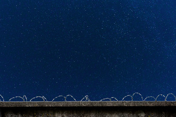 Concrete fence with barbed wire and starry sky