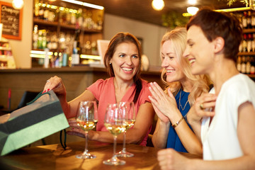 people, leisure and lifestyle concept - women with shopping bags at wine bar or restaurant