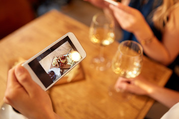 people, technology and lifestyle concept - hand of woman picturing food by smartphone and drinking wine at bar or restaurant