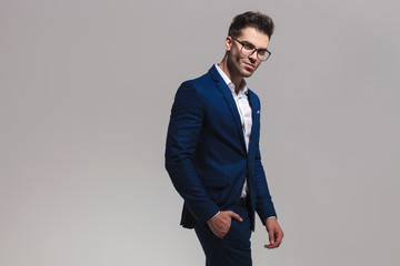 smiling elegant man wearing glasses stands with hand in pocket
