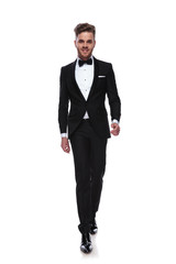 smiling young man in tuxedo and bow tie is walking