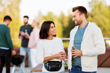 leisure, celebration and people concept - happy couple with drinks in bottles at rooftop party