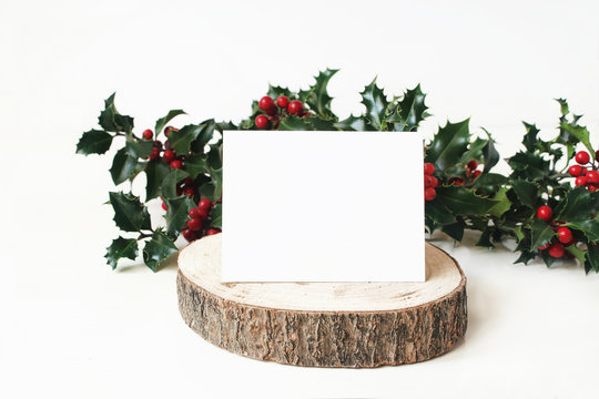 Festive Christmas mockup scene with handmade paper place card on wooden cut board and holly red berries, leaves and branches. White table background. Winter wedding, celebration styled photography.