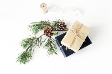 Christmas composition. Festive wrapped Christmas gift boxes with pine branch with cones and silk ribbon on white table background. Winter design. Flat lay, top view.