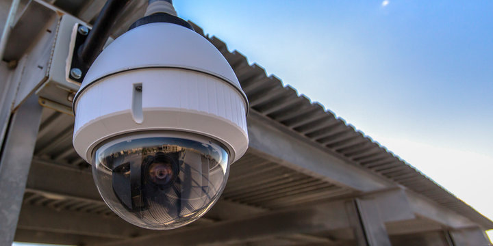 White dome security camera overhanging on a roof