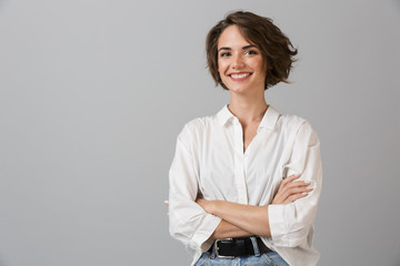 Happy young business woman posing isolated over grey wall background. Fototapete