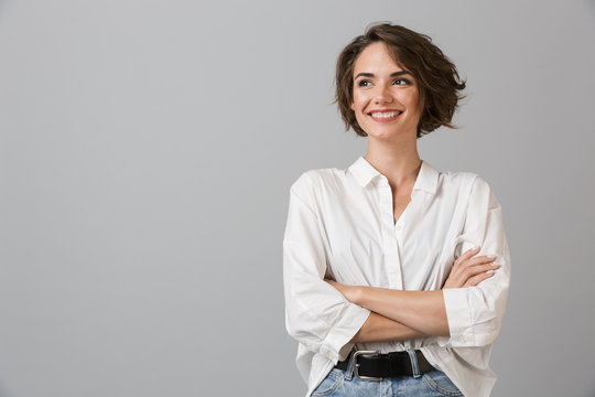 Happy young business woman posing isolated over grey wall background.