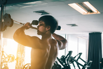 Asian man training at gym and doing pull-ups.