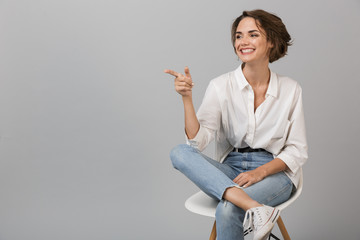 Business woman posing isolated over grey wall