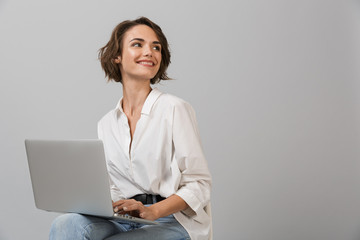 Young business woman posing isolated over grey wall background sitting on stool using laptop computer.