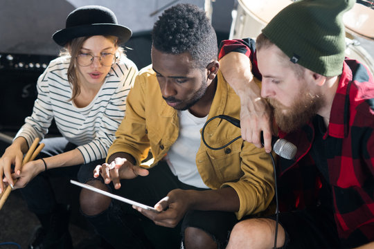 Portrait of three young people using digital tablet while writing music in band rehearsal