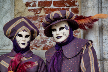 Carnival lilac-beige mask and costume at the traditional festival in Venice, Italy