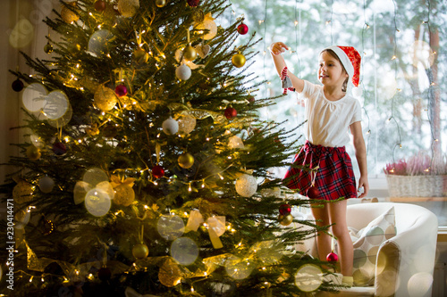 Cute little girl in red Santa hat and plaid skirt decorating Christmas tree at home. Cozy living room decorated with lanterns and Christmas lights.