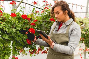 Young florist holding digital tablet