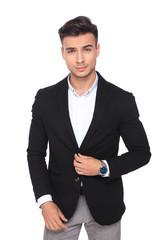 portrait of handsome businessman buttoning his black suit