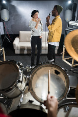 Full length portrait of two young musicians singing during band rehearsal in studio