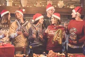 Group of young friends having fun on Christmas party, cheering with champagne and holding letters balloons spelling words Xmas, wearing santa's red hats - winter holidays celebration together concept