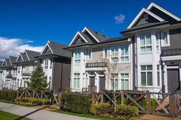 Suburban residential street townhomes. On bright sunny spring day against bright blue sky.