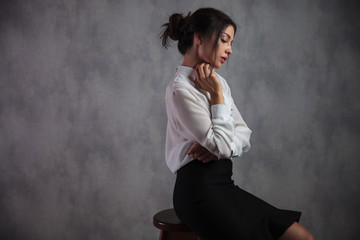 thoughtful or sad elegant woman is sitting