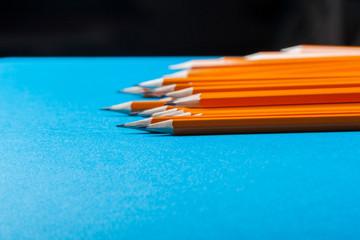 Bunch of orange pencils on blue background close up