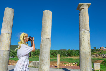 Caucasian female photographing a Greek Temple. Woman takes shots of Doric Propylon entrance of Ancient Messene, Archaeological Site, Peloponnese, Greece. summer travel concept.