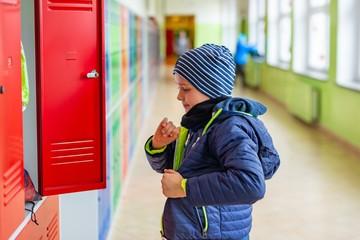 Child boy dressing his autumn jacket in school