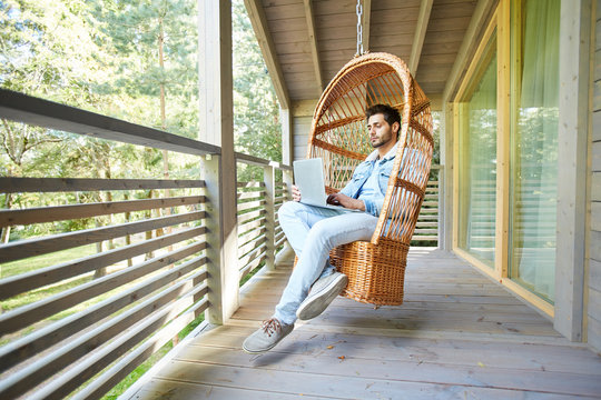 Serious handsome young businessman in casual clothing sitting in hanging armchair and working with laptop on balcony of countryside house