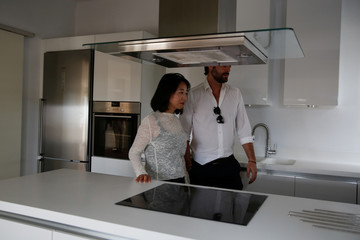 Real estate broker Sotiris Fourtoulakis shows an apartment to Lian Wenmin, 29, a potential buyer from China, in central Athens