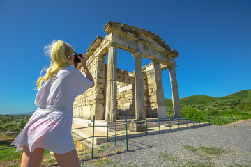 woman photographer with takes shots of Mausoleum, Historical Site of Ancient Messene, Peloponnese, Greece. Seductive female photographing a Greek Temple. Europe summer travel