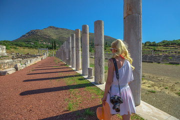 Travel photographer at columns of Ancient Messene Historical Site in Peloponnese, Greece. Seductive female in greek dress photographing the ruins. Holidays lifestyle