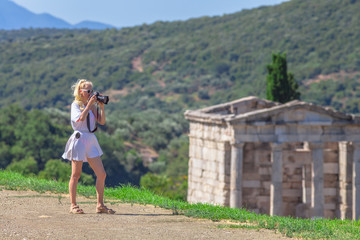 Travel woman photographer in greek dress at Archaeological Site of Ancient Messene, Peloponnese, Greece. Seductive female photographing a Greek Temple. The Mausoleum on blurred backgroung.