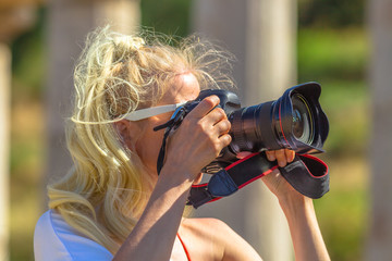 Travel woman photographer in greek dress takes shot of Archaeological Site of Ancient Messene, Peloponnese, Greece. Seductive female photographing a Greek Temple. close up