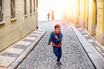 Portrait of a boy running up the street