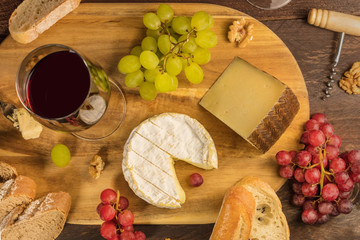A photo of a wine and cheese tasting with bread, grapes, walnuts, and a glass of red wine, shot from the top on a dark rustic wooden background
