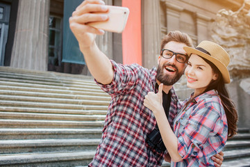 Happy couple stand together and pose on camera. He holds phone. She shows big thumb up. They stand besides stairs.