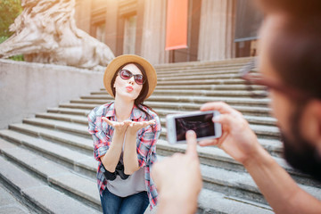 Beautiful young woman poses on camera and sending kisses to young bearded man. She stands on stairs. Guy holds phone in hands. He points on screen.