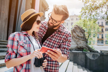 Young man and woman stand together and look at each other through glasses. They smile to each other. Man holds phone while woman points on its screen. She has binoculars.