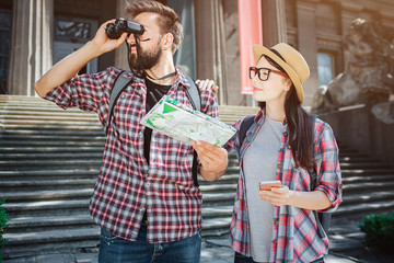 Explorer stand in front and look in binoculars. He holds map in hand. Femle tourist stand besides him and look at young man.